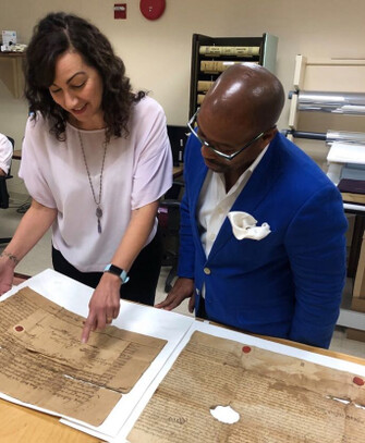 Outreach Conservator Tahe Zalal discusses the preservation of a rare document at the Charleston County South Carolina Register of Deeds with Michael Miller.