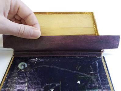 Senka-shi kozo tissue (Hiromi HM-37) was toned with acrylic paints to match the removed leather hinge. It was adhered under the lifted paper on the lower tray with wheat starch paste and then to the detached spine edge wall.
