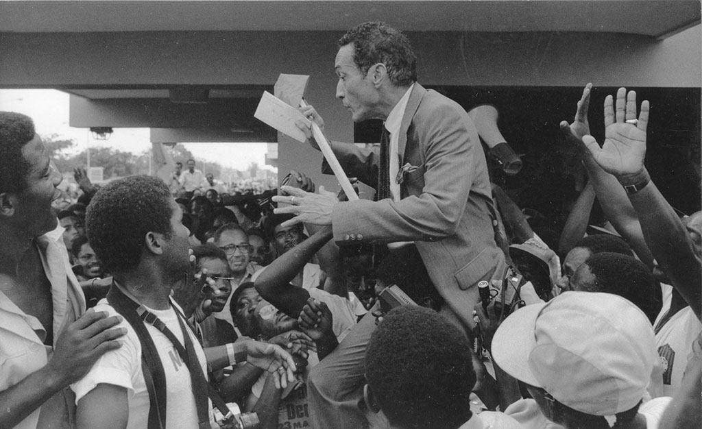 Jean Dominique hoisted in the air by his supporters, upon his return from exile in 1986.