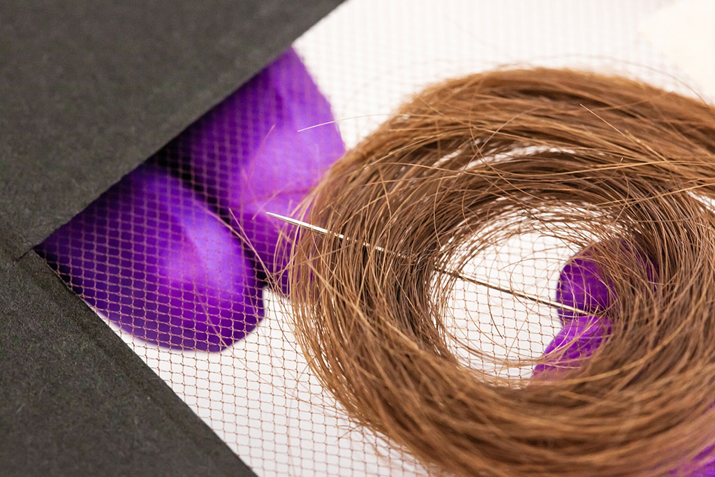 The thread was woven through several layers of hair at varying depths. To avoid strain on the hair, the stitches were kept long and loose.
