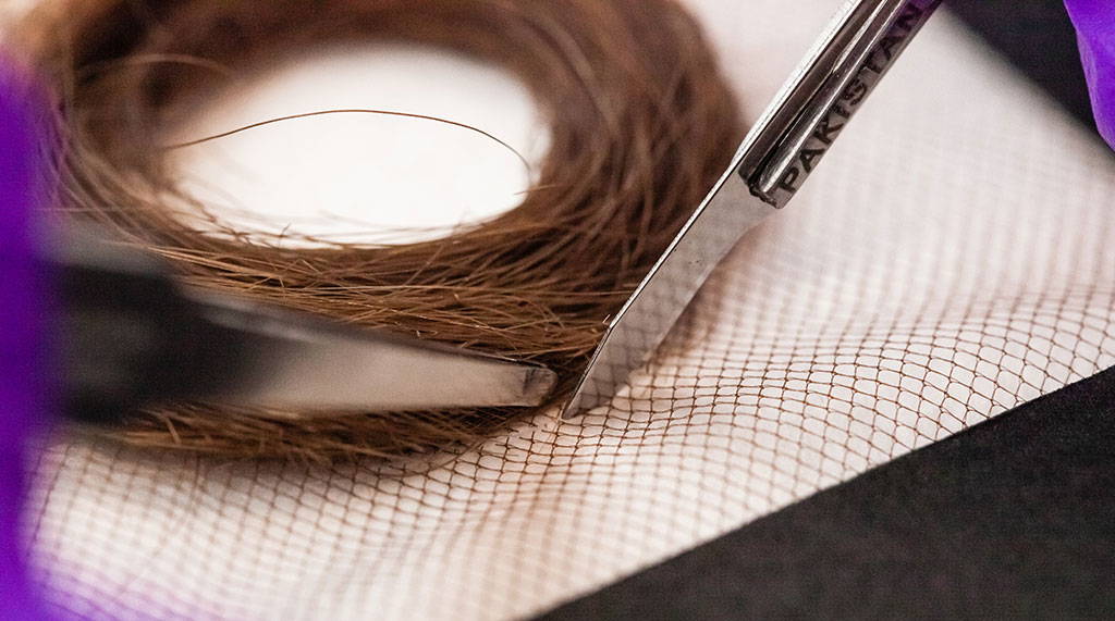 Trimming the net textile using a scalpel. Tweezers were used to hold the hair away from the sharp blade.