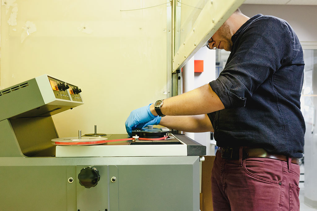 Audio Preservation Engineer Karl Fleck works in the NEDCC fume hood to digitize the tapes.