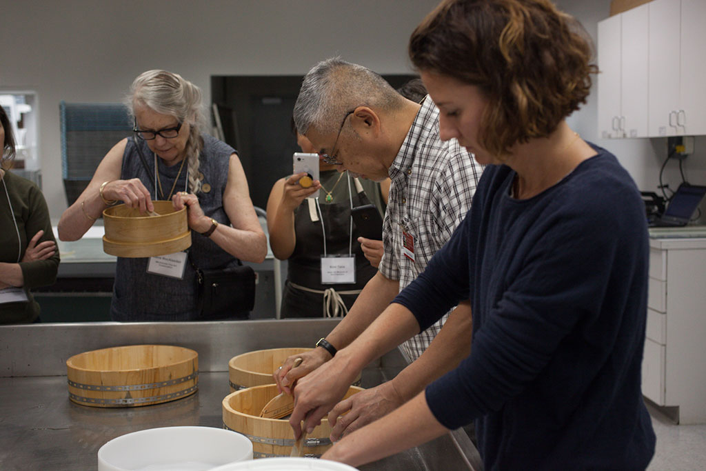 "Angela Campbell, Yoshi Nishio, and Alena MacAlasdair prepare the ""jin shofu"" (wheat starch paste) for use."
