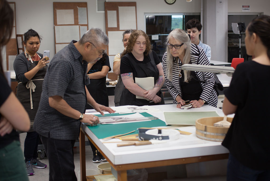 Mr. Nishio determines the appropriate dimensions of the silk brocades for his painting as attendees look on.