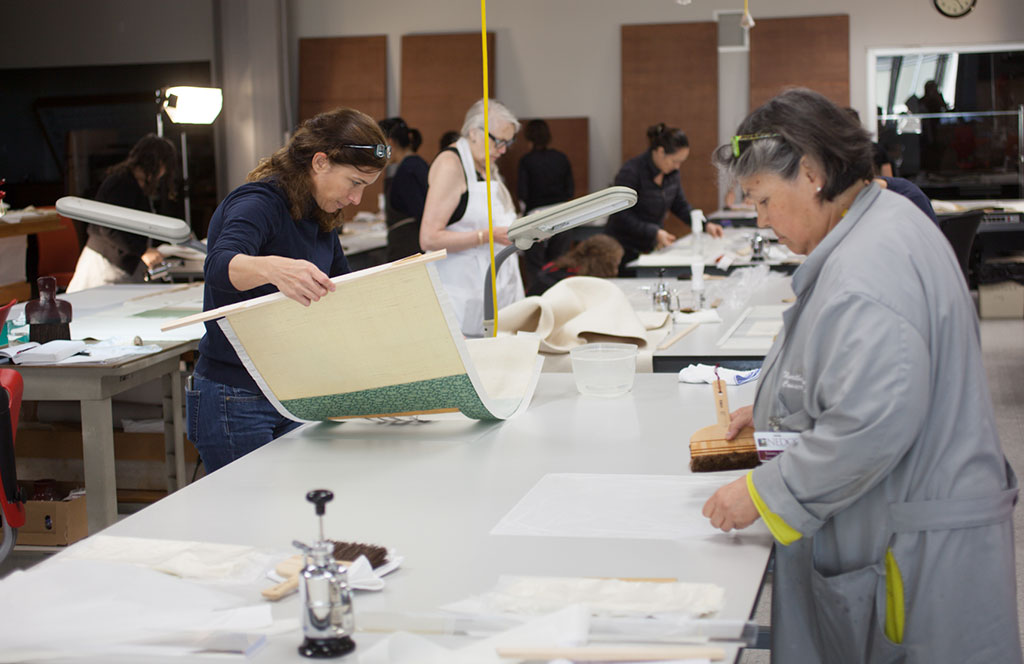 "Luana Maekawa and Deborah LaCamera prepare their ""kakejiku"" (scroll painting) for lining."