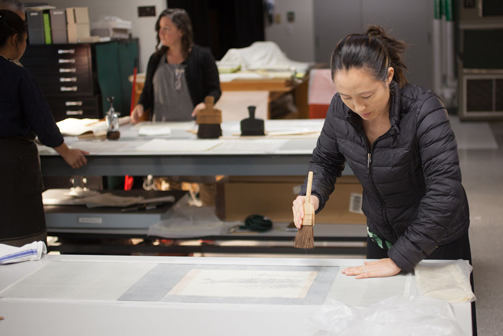 "Erin Jue applies the ""nade-bake"" (smoothing brush) to flatten and smooth out her painting."
