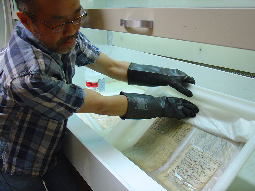 Manuscript record book leaves are washed in filtered water and ethanol to reduce discoloration and acidity of paper.