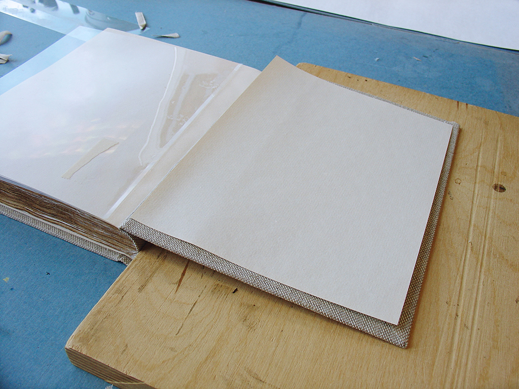 Paper pastedowns of the same handmade paper used for the endsheets are adhered to the insides of the cover boards.